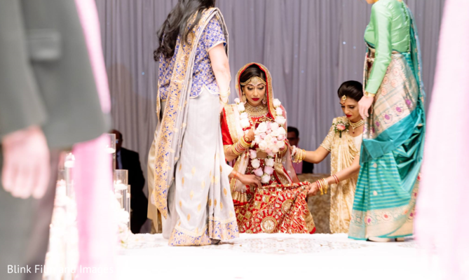 Indian bride getting on stage with the help of her Indian relatives