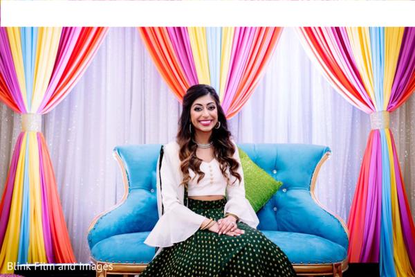Indian bride sitting on a couch with a decorated background