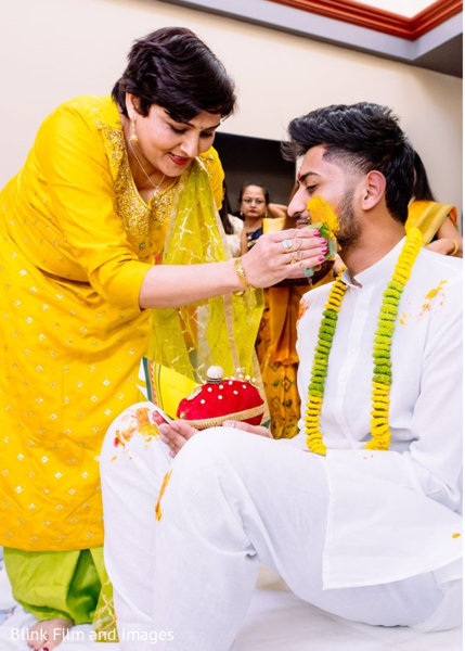 Indian relative applying tumeric paste to the Indian groom's face