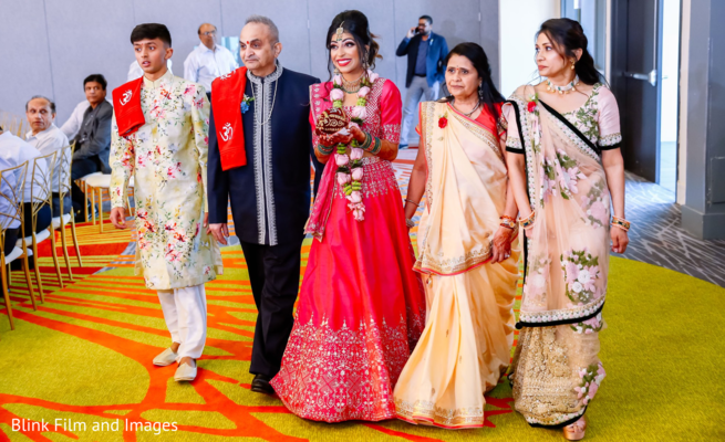 Indian bride entering the hall escorted by her Indian relatives