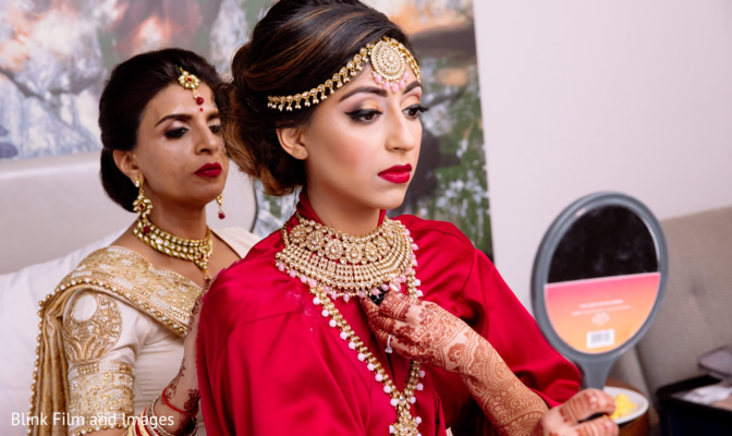 Indian bride trying on jewelry joined by an Indian relative
