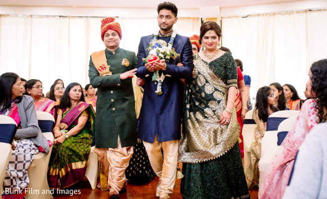 Indian groom walking down the aisle escorted by Indian relatives