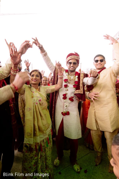 Indian groom and Indian relatives dancing during the Baraat