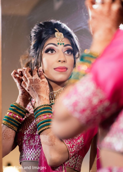 Indian bride putting on her earrings