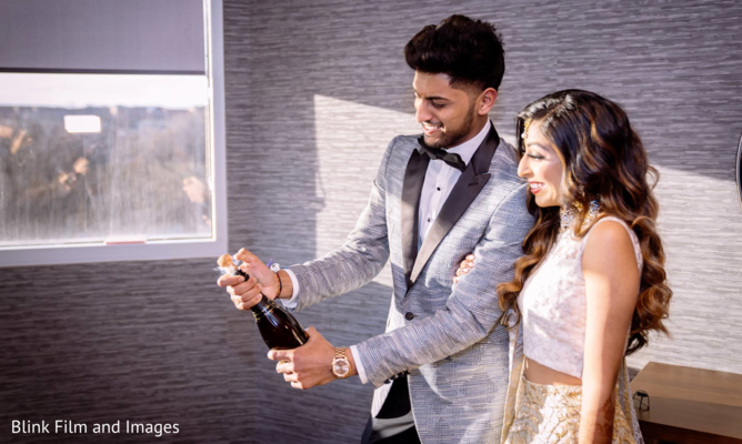 Indian couple about to open a bottle of champagne
