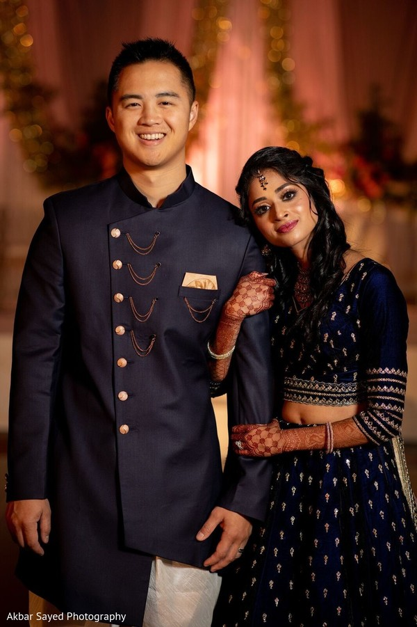Indian groom with bride posing on their reception Indian outfits.