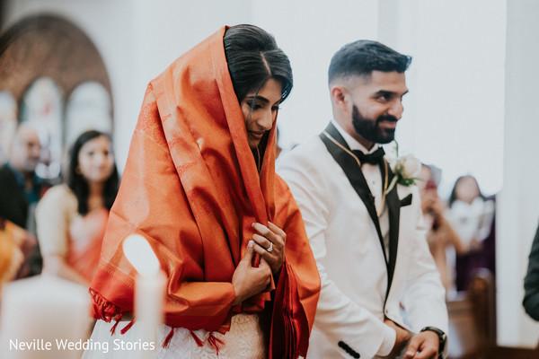 Indian bride wearing her orange ceremony veil next to groom.