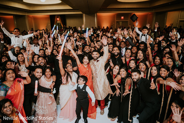 Indian couple with Indian wedding guests photography.