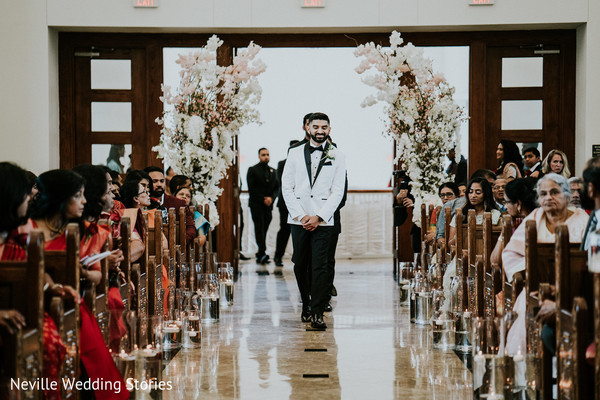 Indian groom walking in down the ceremony aisle.