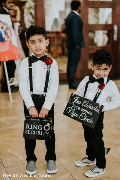 Cute Indian wedding page boys holding ring box and sign.
