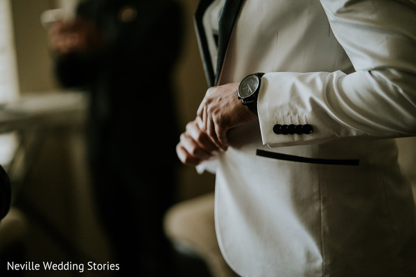 Indian groom putting on his white and black ceremony suit.