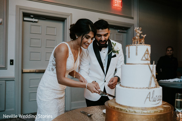 Indian bride and groom cutting white and golden cake.
