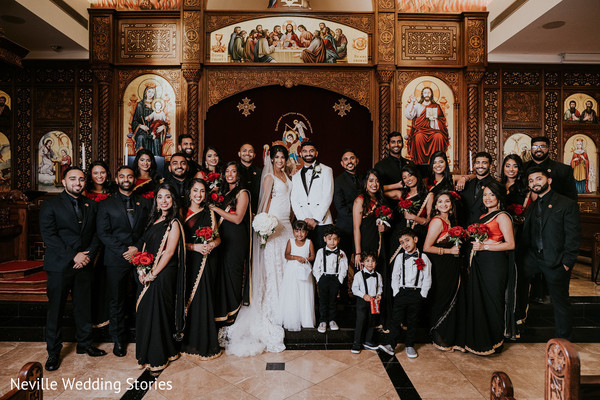 Indian couple with groomsmen, bridesmaids, flower girl and page boys.