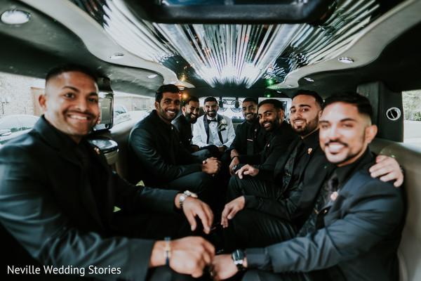 Indian groom with groomsmen inside limousine.