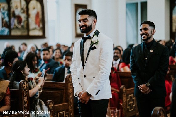 Indian groom walking in down the wedding ceremony aisle.