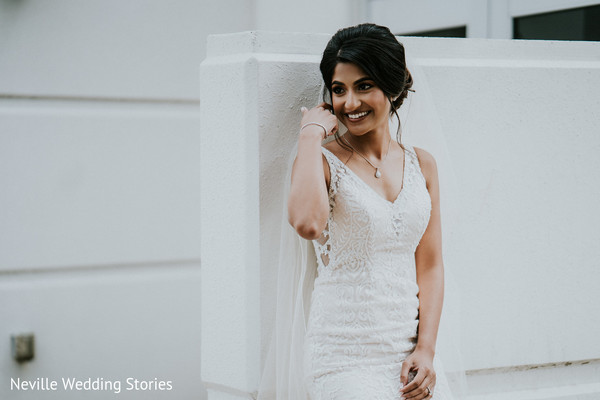 Indian bride posing on her white wedding gown.