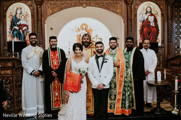 Indian couple posing with priest at wedding ceremony church.