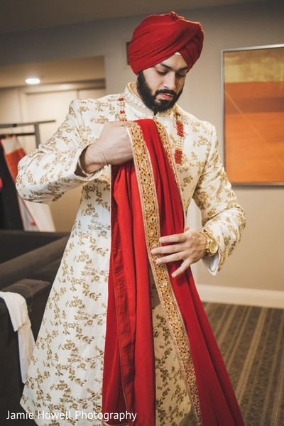 Indian groom putting on his red scarf
