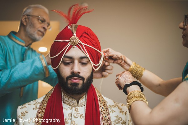 Indian relatives putting a head-dress on the Indian groom
