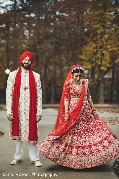 Indian groom smiling while his Maharani shows off her red lengha