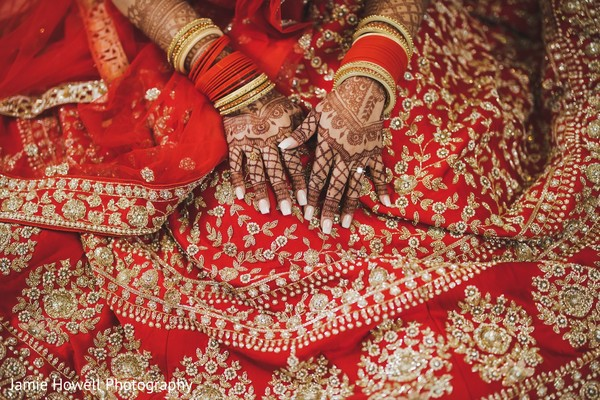 Maharani's henna stained hands over her red and gold lengha