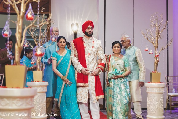 Indian groom walking down the aisle escorted by his Indian relatives