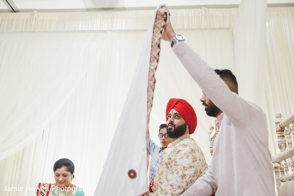 A veil is placed to hide the Indian groom
