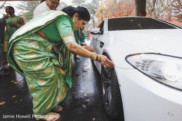 Indian relative inspecting the car outside the venue