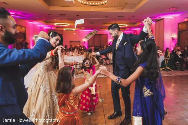 Indian newlyweds dancing with three Indian girls