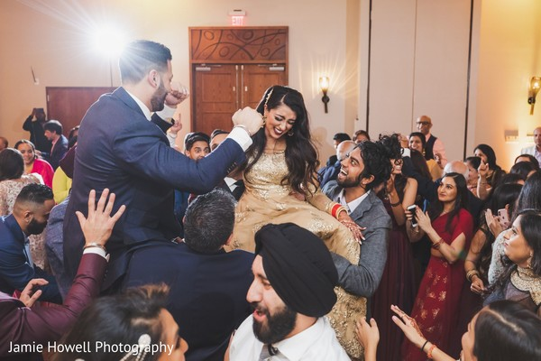 Indian relatives carrying the Indian newlyweds on their shoulders