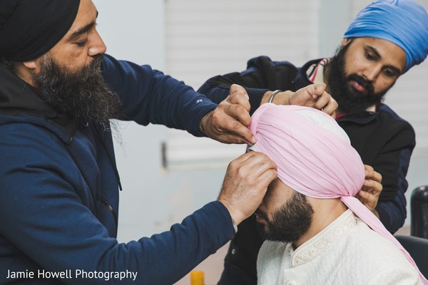Indian relatives adjusting the Indian groom's turban