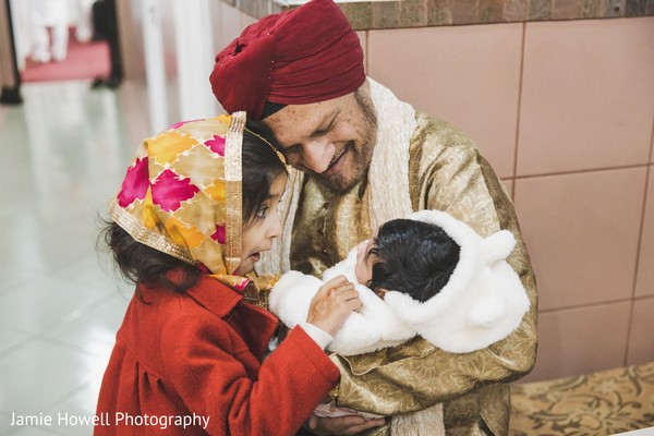 Indian girl looking at a baby on an Indian relative's arms