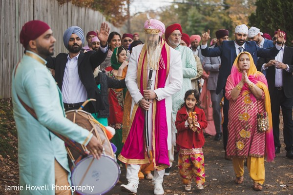 Indian groom and Indian relatives walking towards the wedding site