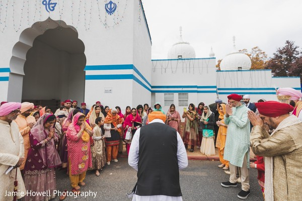 Indian groom and Indian relatives saying a prayer outside the temple