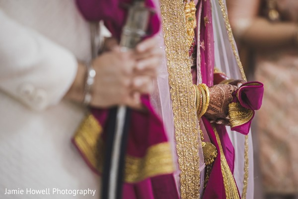 A close up to the hands of the Indian couple during the prayers