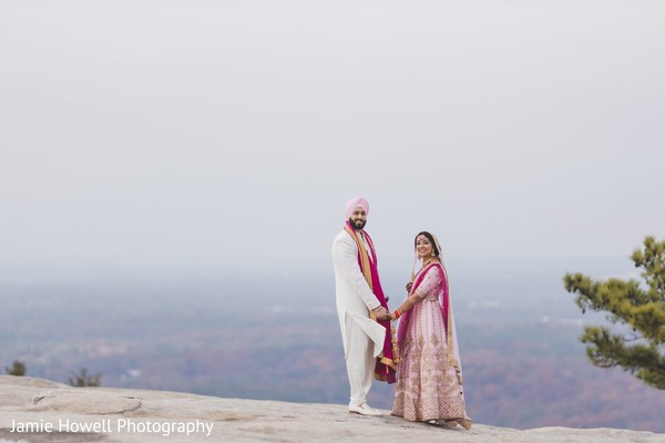 Indian couple holding hand on top of a cliff