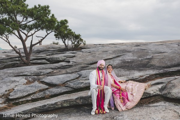 Indian bride leaning on her Indian groom while sitting on the stones