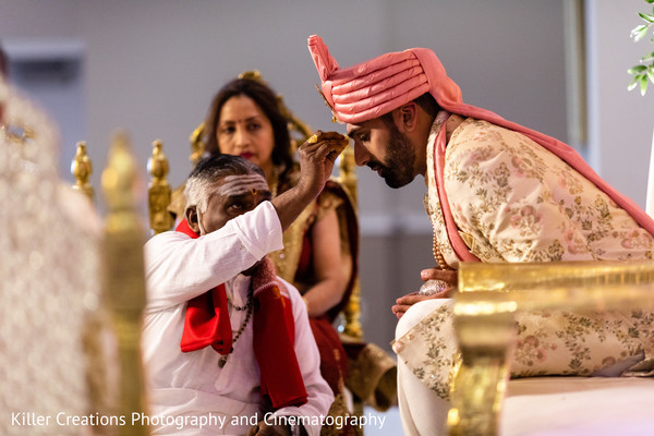 Indian groom receiving the priest blessing.
