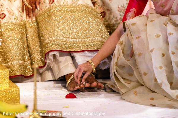 Maharai putting ring on his Indian groom toe.