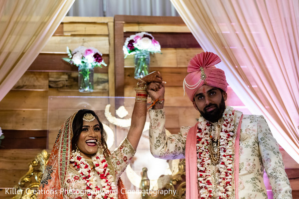 Indian couple raising hands after getting married.