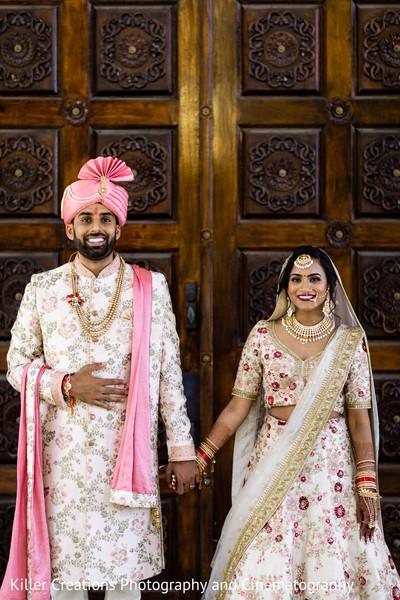 Indian couple in front of a wooden door.