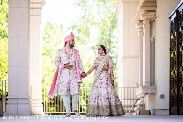Indian couple holding hands and wwalking towards the camera.