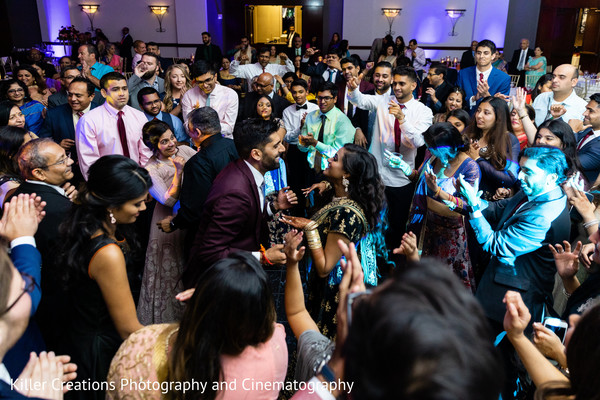 Indian coupe dancing in the middle of their Indian relatives.
