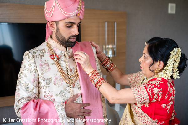 Indian groom being assisted by Indian relative.