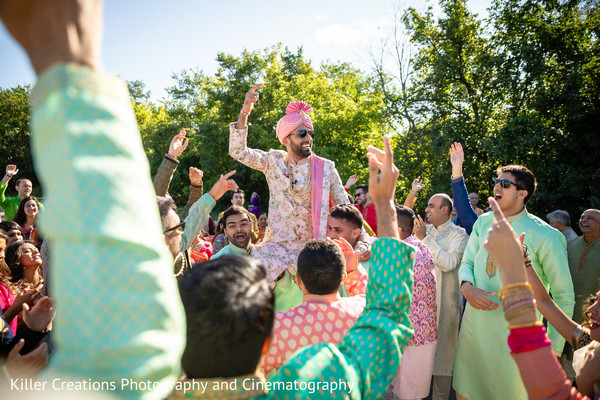 Indian groom waving his hand during Baraat.