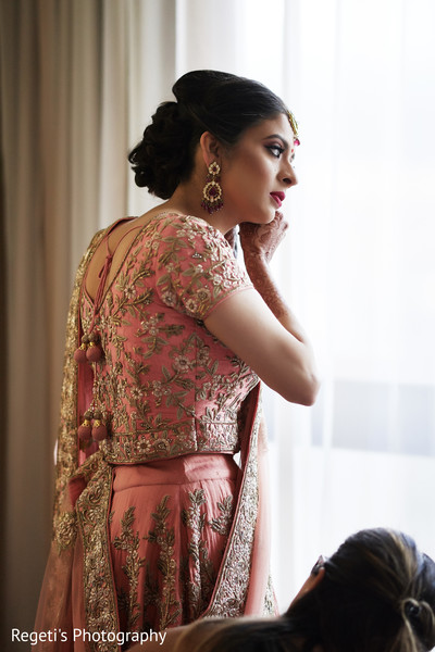 Indian bride putting her earrings.