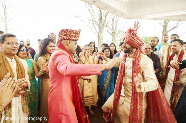 Indian groom dancing with relatives during baraat.