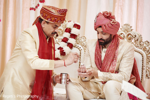 Indian groom receiving gift from relative.