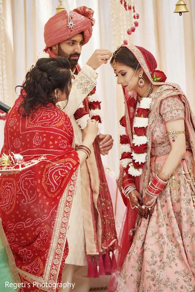 Indian groom putting jewel on his Maharani.
