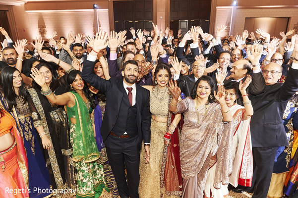 Indian couple and their guests saluting the camera.